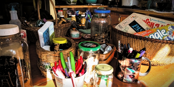 Photo of jars, bottles, baskets. Containerizing allows me to group many objects in a few categories. Easier for my autistic mind and senses.