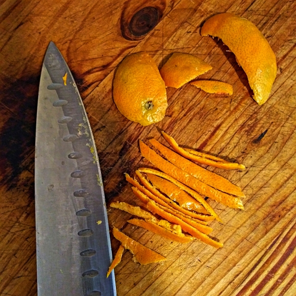 Photo of orange peels and knife. A small amount of sliced lemon & orange peel adds decoration... and flavor. Just remember to scrape the bitter white pith from the inside before slicing.