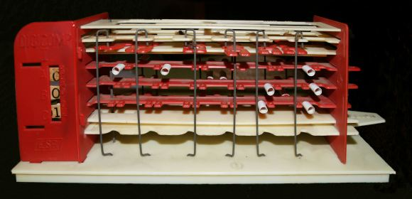 Photo of an original Digi-Comp I plastic, mechanical computer, ca. 1963. It is made of layers of red & black plastic, with wires and small plastic tubes that manipulate gears to literally crank out 1s & 0s. A small window to the left of the machine displays 3 wheels with ones or zeros to show answers from 0 to 7.